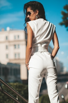 女性モデルの肖像画。白いスーツが路上でポーズの女性。サングラスのファッション女性