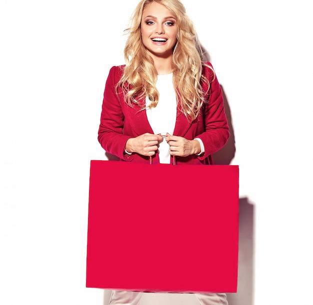 白で隔離される流行に敏感な赤い服で彼女の手で大きなショッピングバッグを保持している美しいかわいい幸せな甘い驚いた金髪女性少女の肖像画