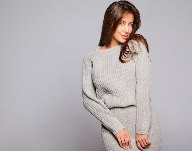 Портрет красивой милой брюнетки модели в повседневной осенней серой одежде свитера без макияжа, изолированной на сером