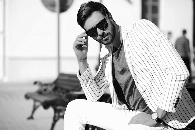 ファッション性の高い外観。サングラスで通りのスーツ布ライフスタイルで若いスタイリッシュな自信を持って幸せなハンサムな実業家モデル