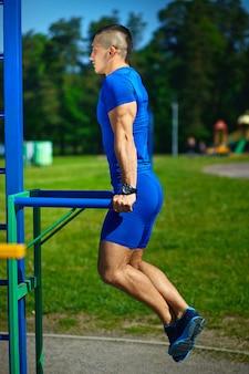 Мужчина красивый здоровый счастливый сильный спортсмен упражнения в городском парке - фитнес-концепции в прекрасный летний день на турнике