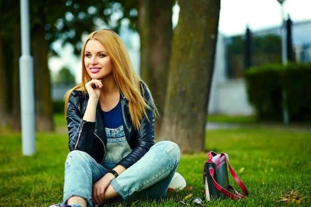 ピンクのバッグとジーンズの公園で屋外に座って明るいモダンな布でかわいい面白いブロンドモダンなセクシーな都市若いスタイリッシュな笑顔の女性女の子モデルの肖像画