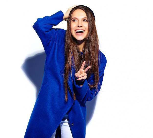 白で隔離スタイリッシュな青いオーバーコートで美しい笑顔ヒップスターブルネットの女性モデル。ピースサインを表示