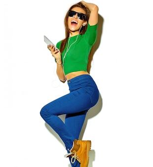 Портрет красивой сумасшедшей улыбающейся брюнетки девушки в повседневной зеленой хипстерской летней одежде без макияжа, изолированной на белом в темных очках, слушающей музыку в смартфоне с наушниками