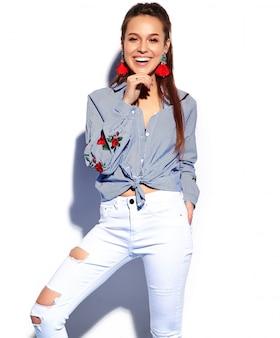Портрет красивой улыбающейся хипстерской брюнетки модели женщины в повседневной стильной синей одежде, изолированной на белом