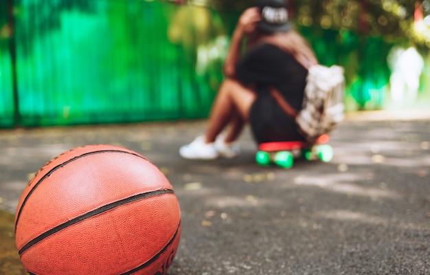 アスファルトの上のプラスチック製のオレンジペニーショートボードに座っている女の子とクローズアップ写真バスケットボール