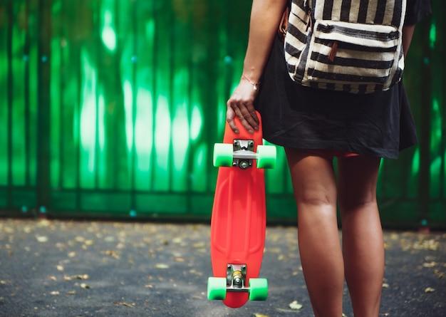 Молодая девушка с пластиковой оранжевой копеечкой за зеленой стенкой