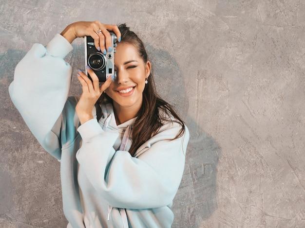彼女のレトロなカメラを使用して写真を撮る美しい若い笑顔写真家の女の子。