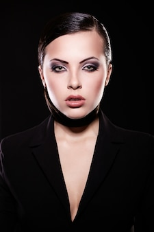ファッション性の高い外観。明るいメイクとジューシーな唇と黒のジャケットで美しいブルネットの少女モデルの肖像画。きれいな肌。黒に分離