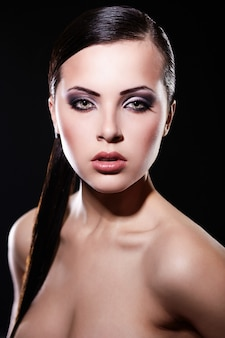 ファッション性の高い外観。明るいメイクとジューシーな唇と美しいブルネットの少女モデルの肖像画。きれいな肌。黒に分離