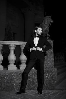 Портрет моды элегантный длинноволосый молодой человек. привлекательная и красивая мужская модель в черном костюме с усами на улице ночью