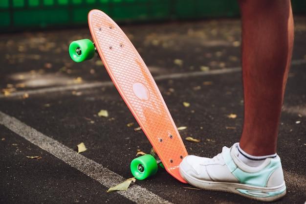 Крупным планом ноги человека кроссовки едет на оранжевом пенни скейтборд на асфальте