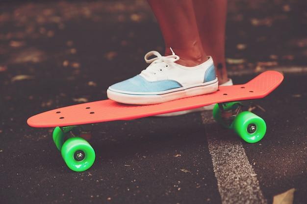 Крупным планом ноги девушки кроссовки едет на оранжевом пенни скейтборд на асфальте