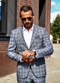 通りでポーズをとってエレガントな市松模様のスーツに身を包んだハンサムなファッション実業家モデル