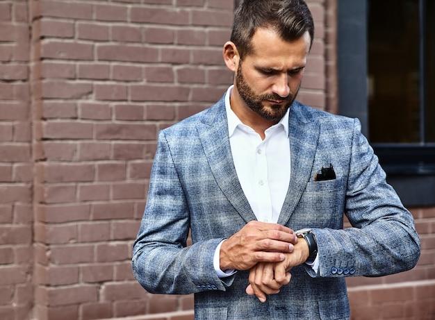 Красивый модный бизнесмен модель одет в элегантный клетчатый костюм позирует на улице