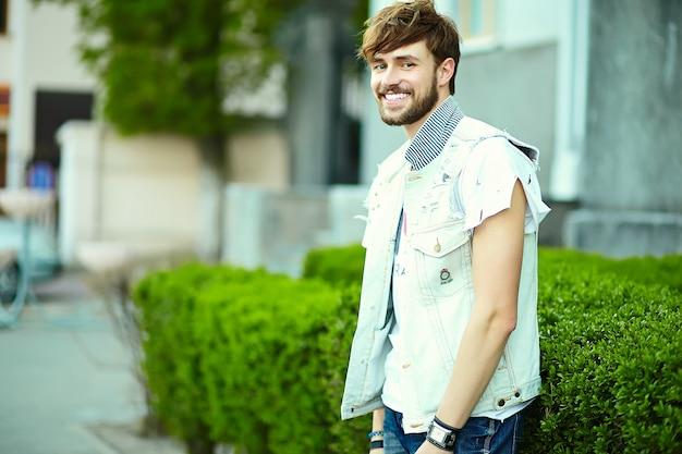 スタイリッシュな流行に敏感な服でハンサムな男の肖像。通りでポーズをとって魅力的な男