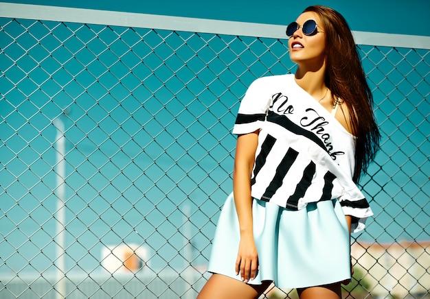 面白いクレイジーグラマースタイリッシュなセクシーな笑みを浮かべて美しい若い女性モデルの明るいヒップスター夏のカジュアルな服装で青い空の後ろの通り