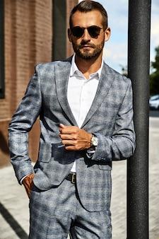 Портрет модельер красивый бизнесмен, одетый в элегантный клетчатый костюм позирует на улице