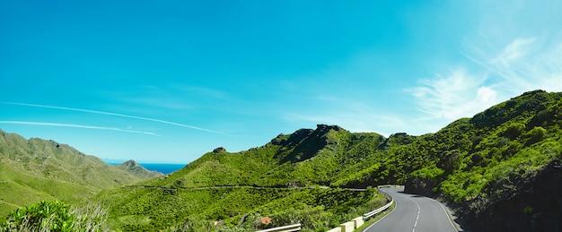 山とアスファルト道路の青い空のパノラマと美しい景色は、青いフィヨルドと苔の山の間を曲がりくねっています。