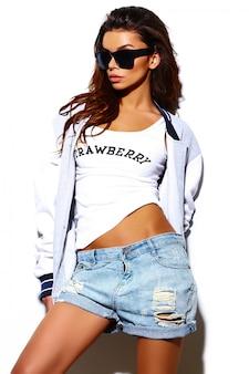 ファッション性の高い外観。サングラスで夏の明るい流行に敏感な布でグラマースタイリッシュな美しい若いブルネットの女性モデル