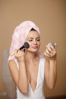 鏡で化粧を適用する頭の上のタオルで美しい若い女性