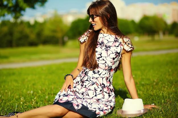 Смешная стильная улыбающаяся красивая модель молодой женщины в летнем ярком платье из ткани в шляпе в парке