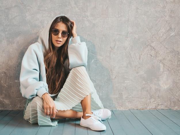 探している若い美しい女性。カジュアルな夏のパーカーとスカートの服でトレンディな女の子。床に座って