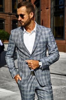 Портрет сексуальный красивый модный бизнесмен модель, одетый в элегантный клетчатый костюм, позирует на фоне улицы. метросексуал