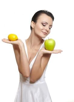 白で隔離されるフルーツレモンと青リンゴと美しい幸せな笑みを浮かべて少女の肖像画