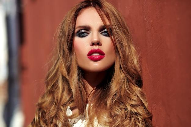 Портрет красоты очарования красивой чувственной кавказской модели молодой женщины с вечерним макияжем в белом летнем платье позирует на фоне улицы возле красной стены