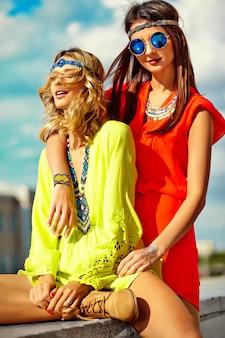 Фасонируйте портрет молодых моделей хиппи женщин в солнечный летний день в яркой красочной одежде битник