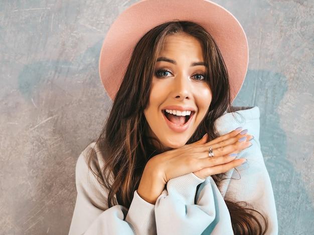 口の近くの手で見ている若い美しい驚く女性。カジュアルな夏服と帽子でトレンディな女の子。灰色の壁に近いポーズの女性