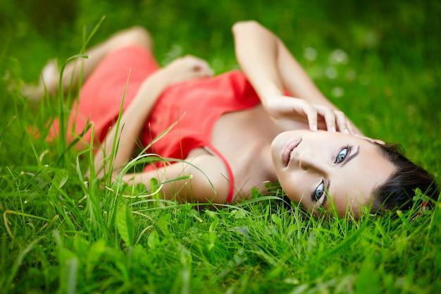 赤いドレスを着てメイクで公園の緑の夏の明るい草で横になっている美しいブルネットの女性モデル。