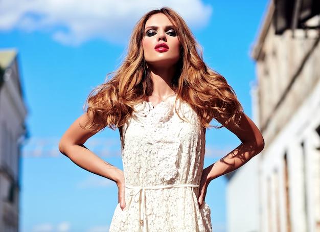 路上でポーズをとって白い夏のドレスで夜のメイクと美しい官能的な白人の若い女性モデルの容姿の美しさの肖像画