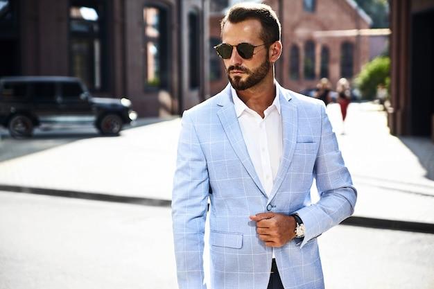 通りでポーズをとってエレガントな青いスーツに身を包んだハンサムなファッション実業家モデル