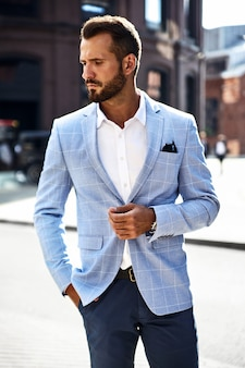Красивый модный бизнесмен модель в элегантном синем костюме позирует на улице