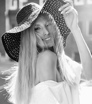白いドレスと夕日の背後にある通りの背景にポーズをとって夏のビーチ帽子に身を包んだ官能的な金髪の女性モデルの肖像画