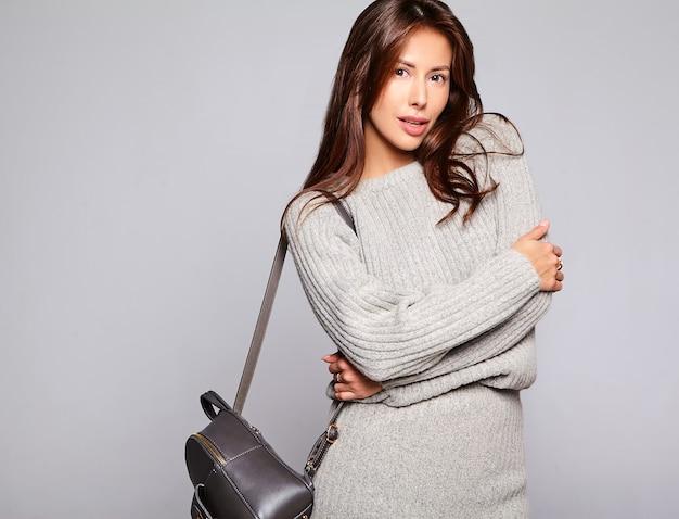 Портрет красивой милой брюнетки модели в повседневной осенней серой одежде свитера без макияжа изолирован на сером с сумочкой