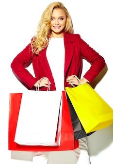 Портрет красивые милые счастливые сладкие улыбающиеся блондинка девушка держит в руках большие покупки красочные сумки в красной куртке битник, изолированных на белом
