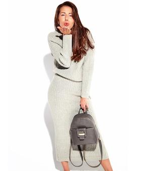 Портрет модели красивая милая брюнетка женщина в одежде свитер случайные осени серый без макияжа, изолированные на белом с сумочкой. дарить поцелуй
