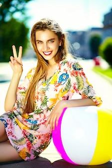 カラフルなボールが通りに座っている夏の明るい流行に敏感な布ドレスで面白いスタイリッシュなセクシーな笑顔の美しい若い女性モデル