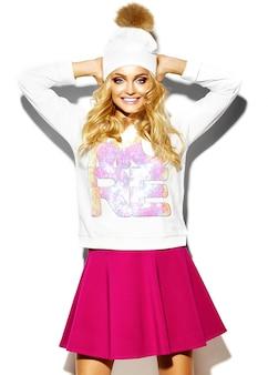 Портрет красивой счастливой сладкой милой улыбающейся блондинки женщины в повседневной хипстерской одежде, в розовой юбке и зимней теплой шапочке