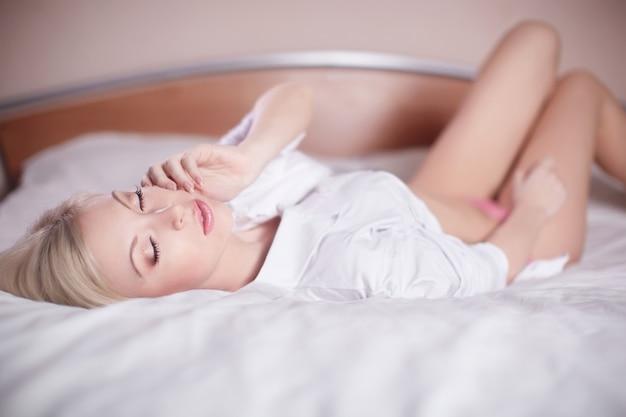 裸のベッドに横たわる美しい官能的なセクシーな若いブロンドの女性