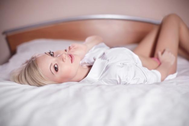 Красивая чувственная сексуальная молодая блондинка лежит в постели голая