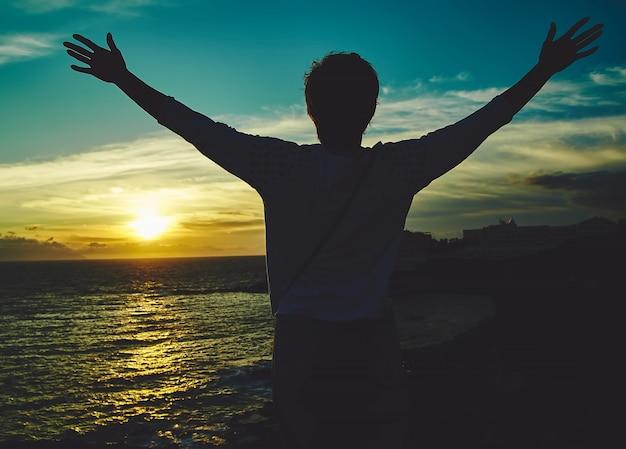 Молодая женщина с поднятыми руками, приветствие солнцу