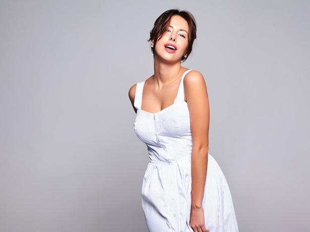 Портрет красивой милой брюнетки модели в повседневном летнем платье без макияжа, изолированном на сером
