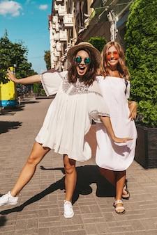 Мода портрет двух молодых стильных хиппи брюнетка и блондинка модели женщин в солнечный летний день в белых одеждах битник позирует