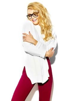 Портрет красивой счастливой сладкой милой улыбающейся блондинки женщины в повседневной хипстерской теплой белой одежде свитера, в очках обнимает себя