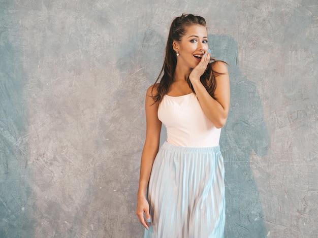 顔の近くの手で見ている若い美しい驚く女性。カジュアルな夏服でトレンディな女の子。灰色の壁に近いポーズの女性