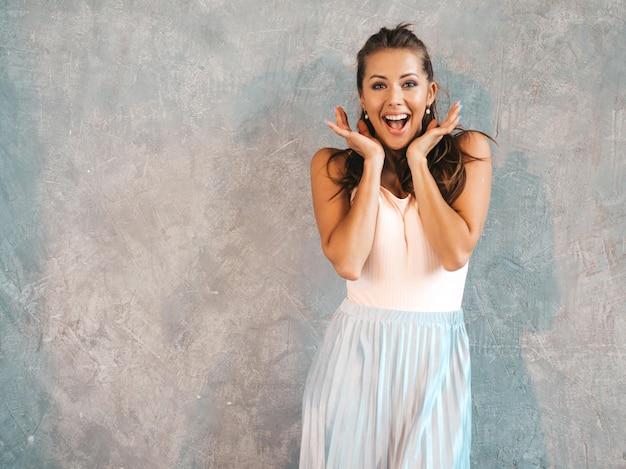 顔の近くの手で見ている若い美しい驚く女性の肖像画。カジュアルな夏服でトレンディな女の子。灰色の壁に近いポーズをとってショックを受けた女性